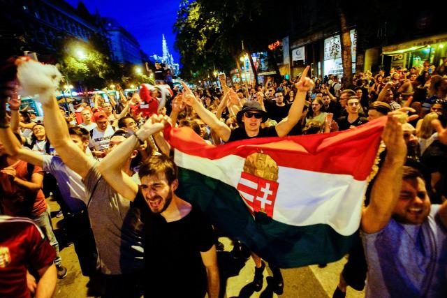 a7a01fa374 Szurkolók ünnepelnek Budapesten, az Erzsébet körúton, miután a magyar  válogatott 2-0-ra legyőzte Ausztria csapatát a franciaországi ...